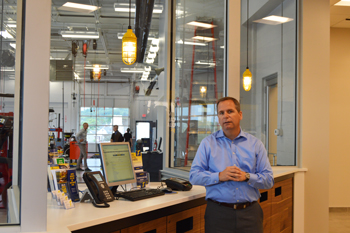 Fred Thomas, vice president and general manager of Goodyear Retail, stands near a customer kiosk in the newly renovated Goodyear Auto Service location at Summit Mall.